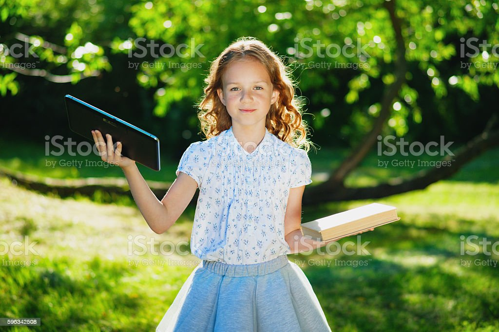 Little girl with digital tablet and book royalty-free stock photo