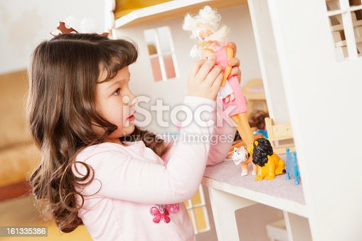 A little girl playing with a dollhouse.