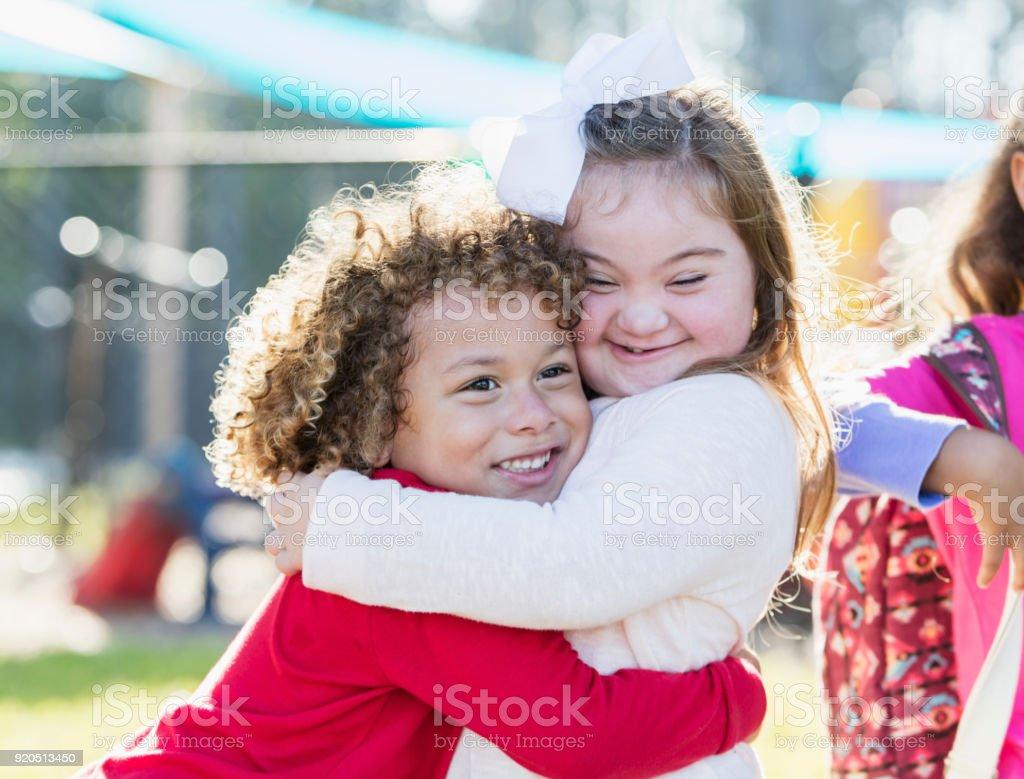 Kleines Mädchen mit Down-Syndrom und jungen umarmt – Foto