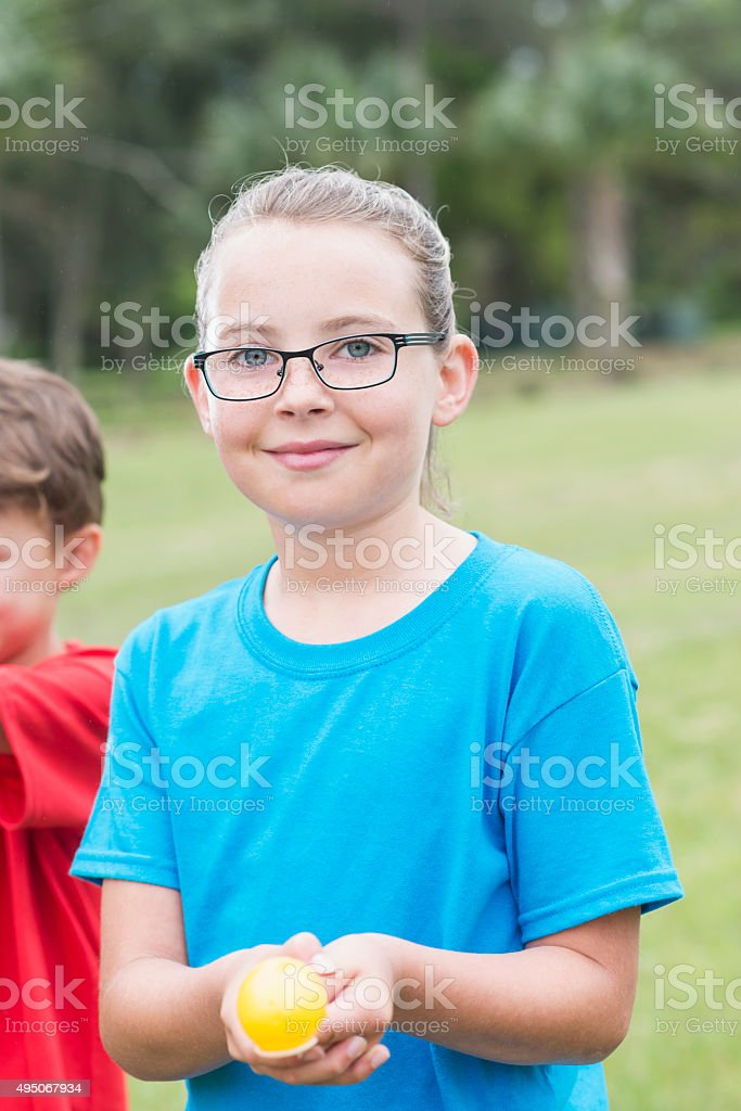 Little girl with eyeglasses in an egg spoon race stock photo