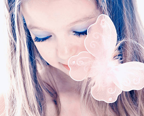 Little girl with eyes closed and butterfly on hair stock photo