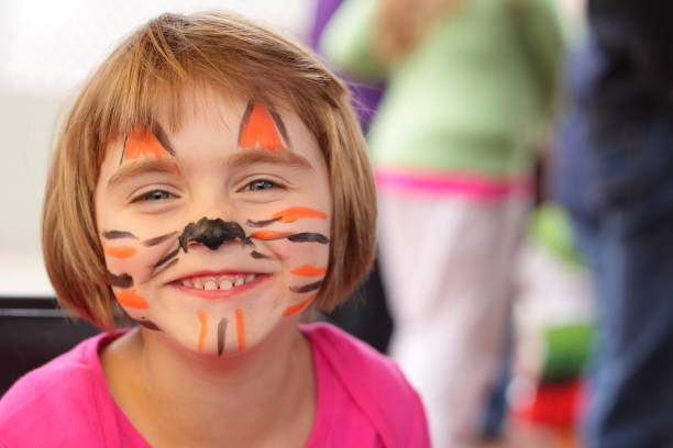 little girl with face painted like tiger smiles at camera - school fete stock photos and pictures