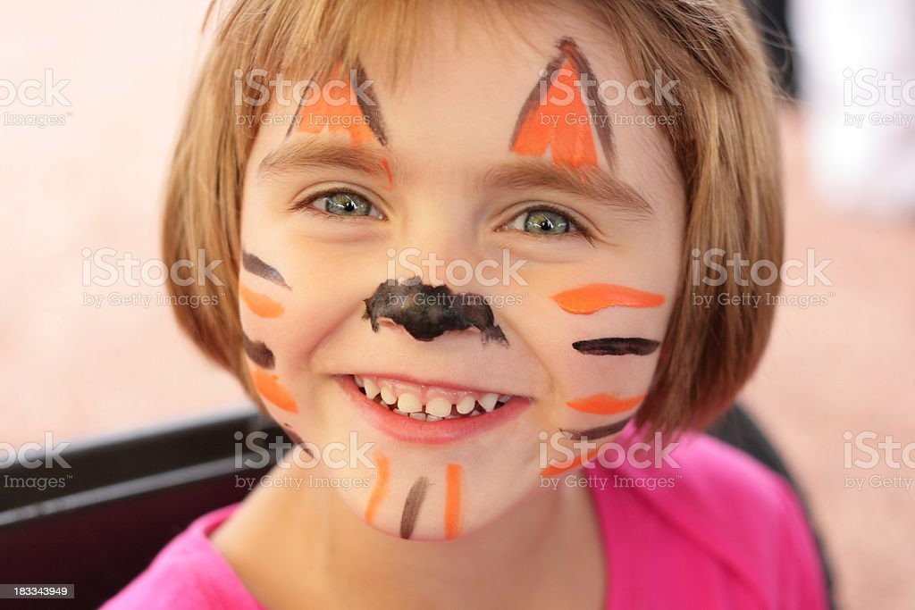 Little girl with face painted like tiger smiles at camera royalty-free stock photo