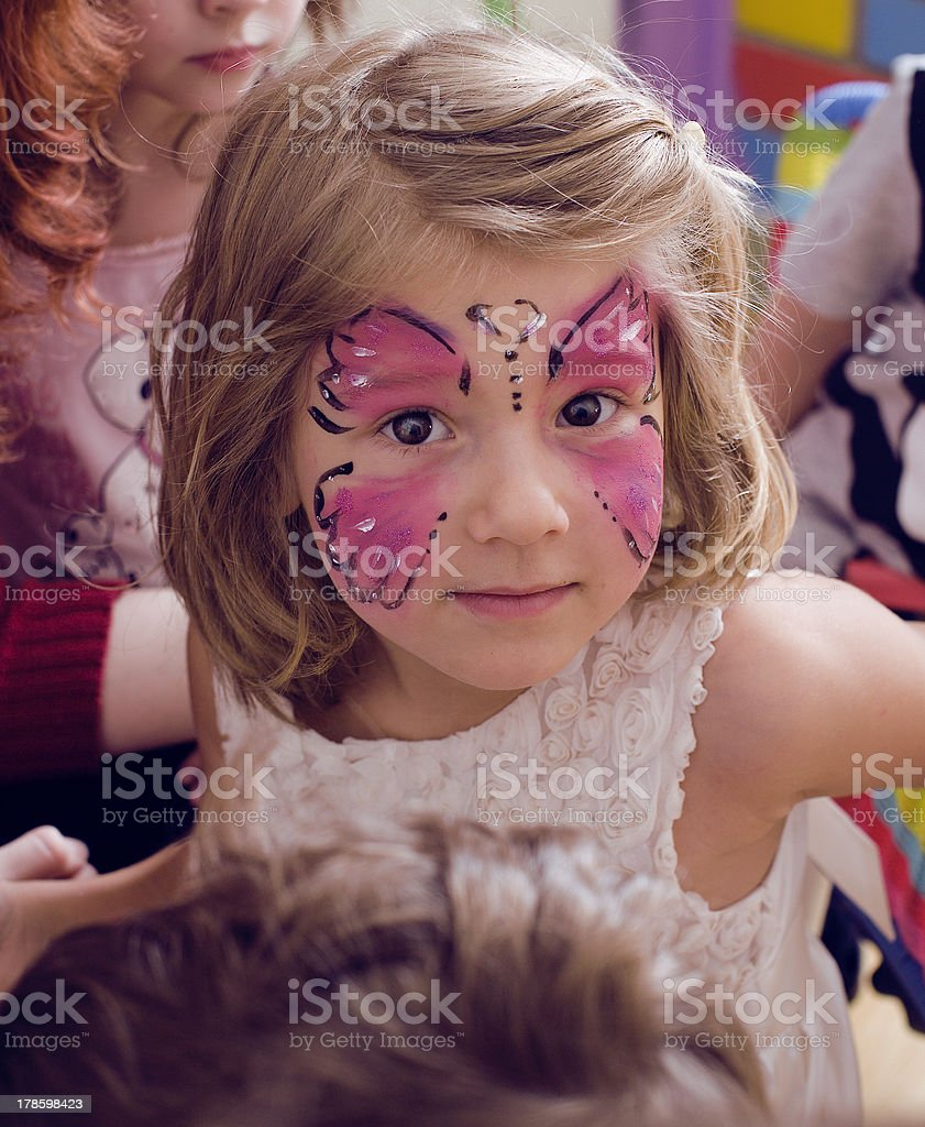 little girl with faceart on birthday party stock photo