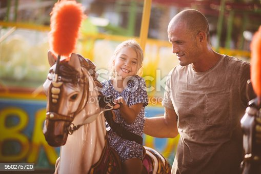 Happy little girl with father having fun riding horse on carousel carnival ride in summer