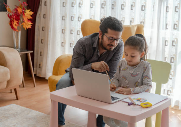 Little girl with father homeschooling and distance learning at home stock photo