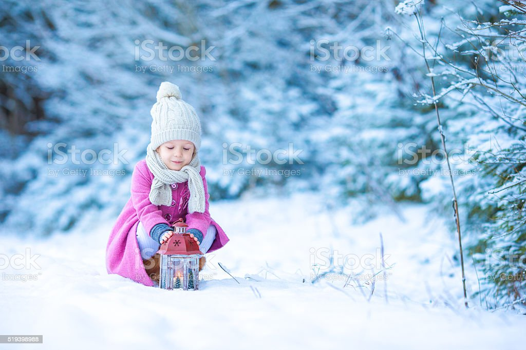Little girl with flashlight and candle in winter day outdoors stock photo