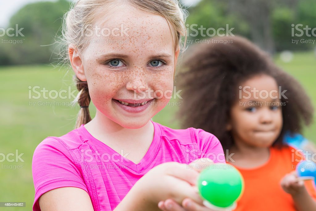Little girl with freckles in an egg spoon race stock photo