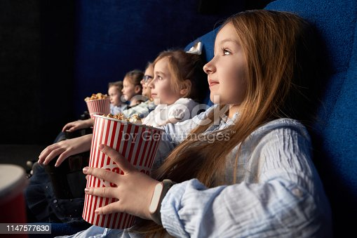 istock Little girl with friends sitting in cinema. 1147577630