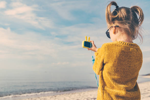 little girl with funny ponytails is taking pictures of the sea. stock photo