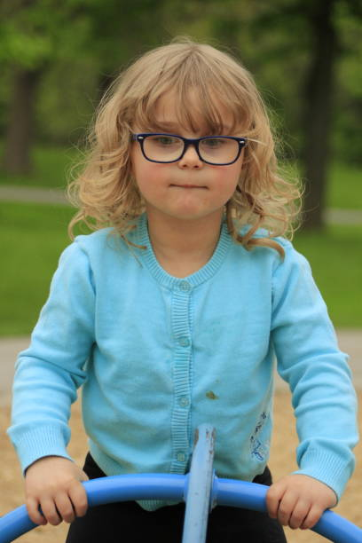 Little girl with glasses and a blue shirt playing on a playground at school aged 3 to 5 stock photo