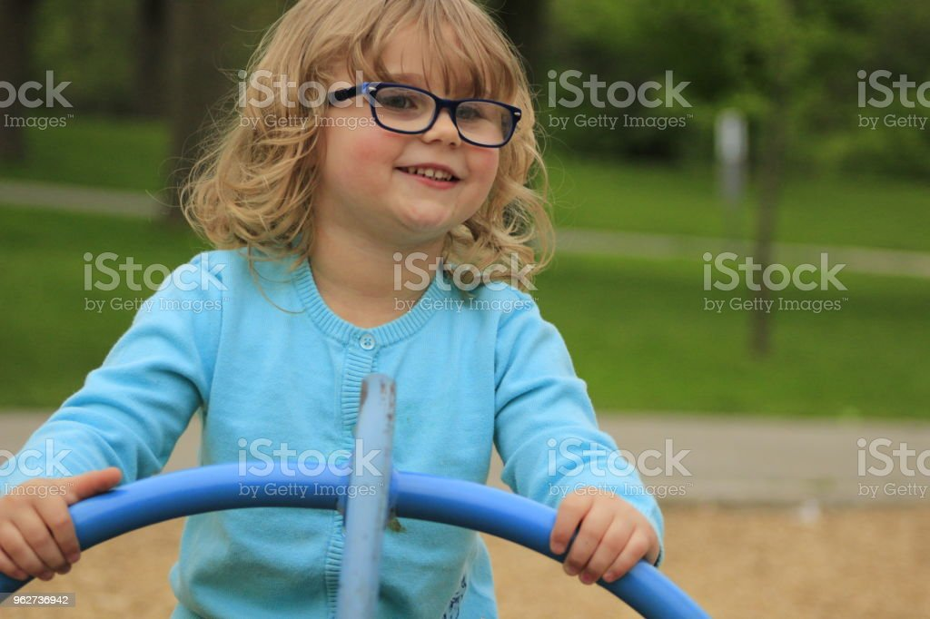 Little girl with glasses and a blue shirt playing on a playground at school aged 3 to 5 - Foto stock royalty-free di 2-3 anni
