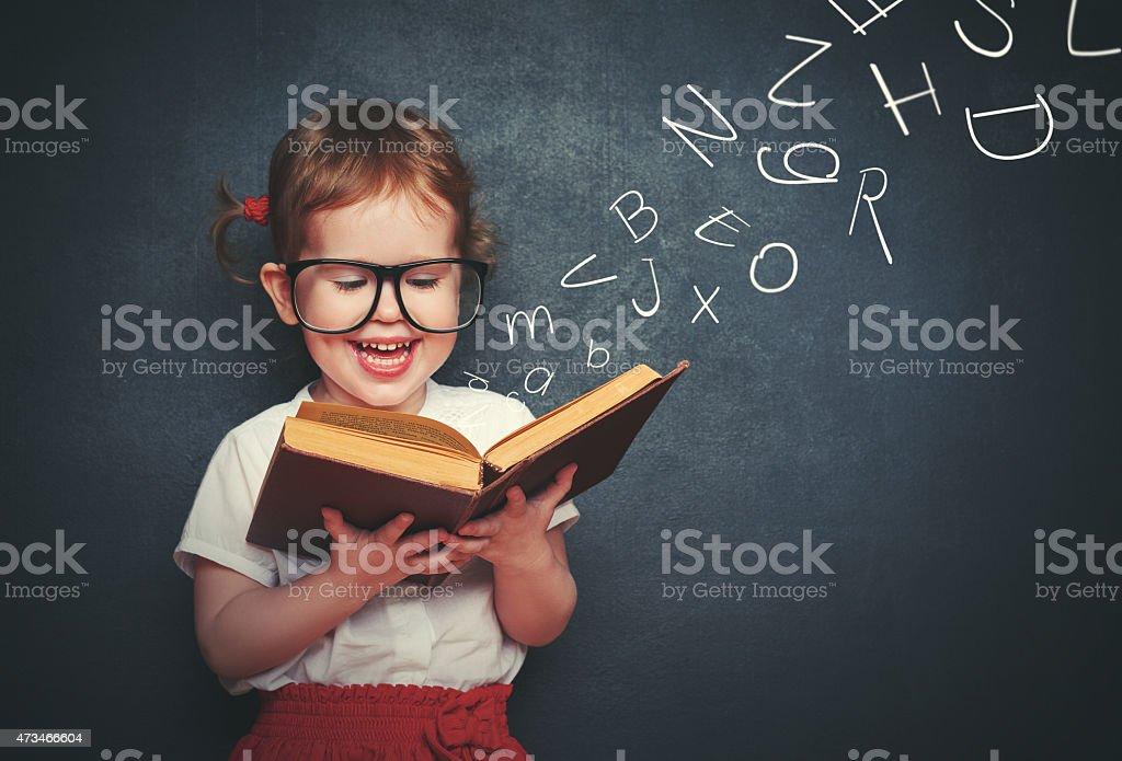 Kleines Mädchen mit Brille lesen ein Buch, mit Abreise Buchstaben - Lizenzfrei 2015 Stock-Foto