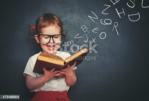 istock little girl with glasses reading a book with departing letters 473466604