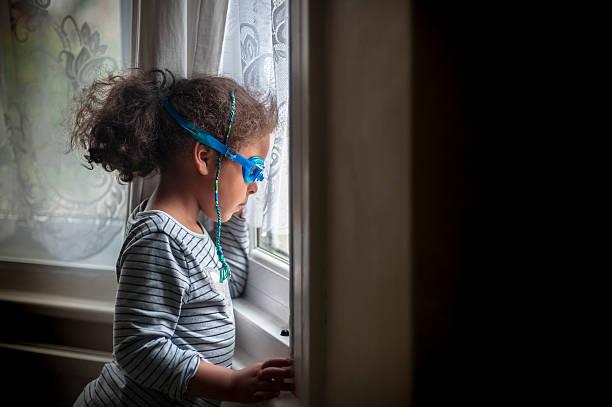 little girl (4-5) with goggles on looking through window - mädchenraum vorhänge stock-fotos und bilder