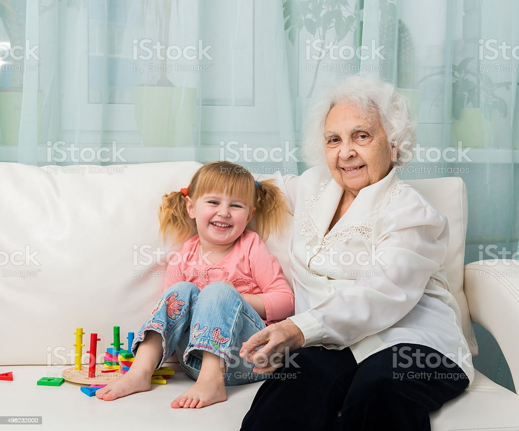 little girl with grandmother on a sofa stock photo
