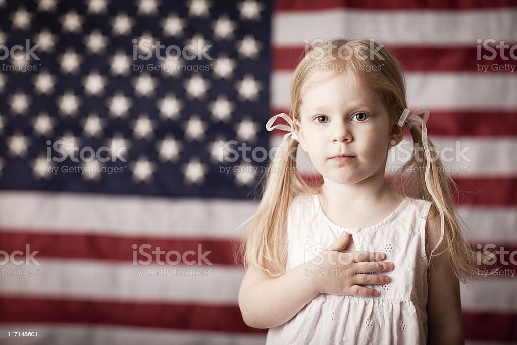 Little Girl with Hand on Heart by American Flag Color photo of a little blond-haired girl with her hand on her heart in front of an American flag. 2-3 Years Stock Photo