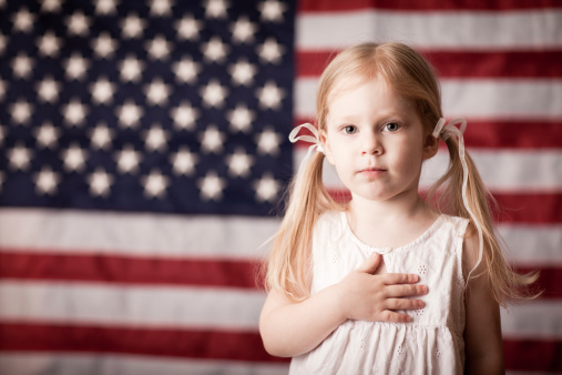 Little Girl With Hand On Heart By American Flag Stock Photo - Download Image Now
