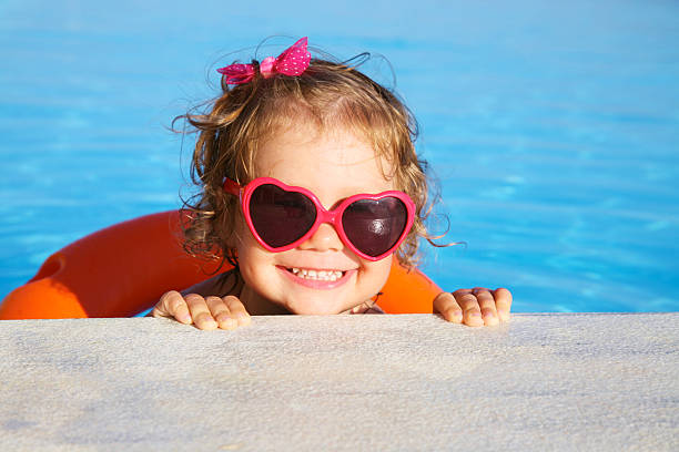 Kleines Mädchen, Sonnenbaden am pool – Foto