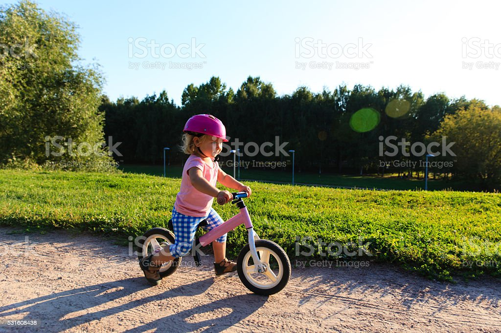 little girl with helmet riding bike at sunset stock photo