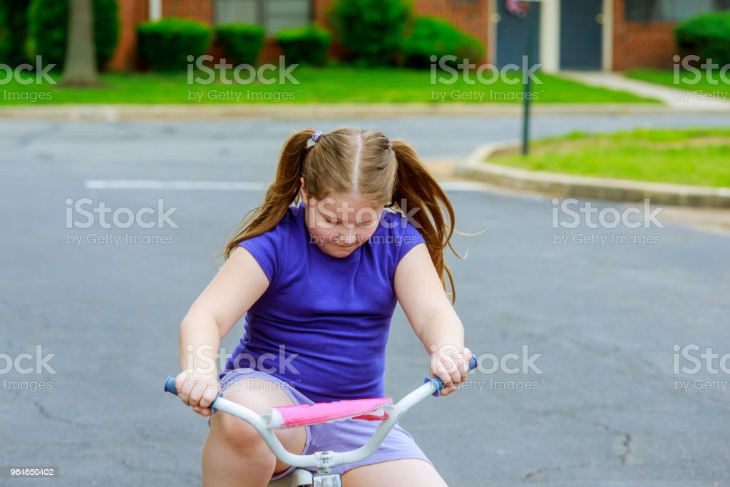 little girl with her bicycle A 5 year old girl is riding a bike on a path through a park royalty-free stock photo
