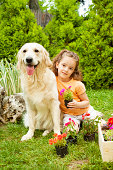 Portrait of an cute little girl gardening with her pet, dog retriever sitting on the grass.