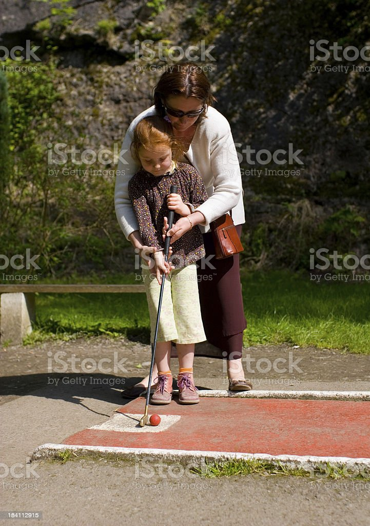 """Little girl with her mother, learning to play mini-golf """"Little 5 year old girl, bending over for her first game of mini golf. Mother helps and shows the way."""" Activity Stock Photo"""