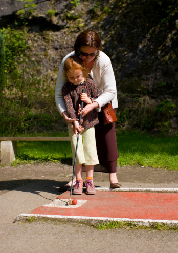 Little Girl With Her Mother Learning To Play Minigolf Stock Photo - Download Image Now