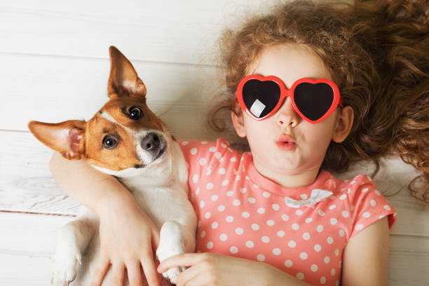 Little girl with her puppy Jack russell terrier lying on a wooden floor. – Foto