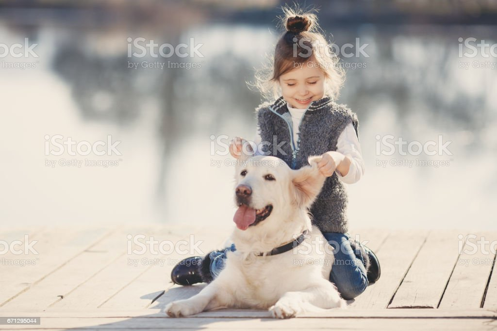 Little girl with his beloved dog at the lake stock photo
