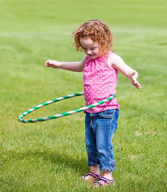 kleines mädchen mit hula-hoop - denim caprihosen stock-fotos und bilder