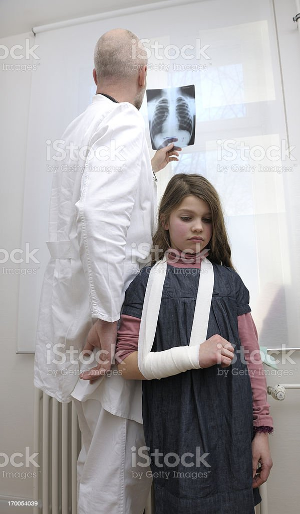 little girl with injured arm in doctor's office royalty-free stock photo