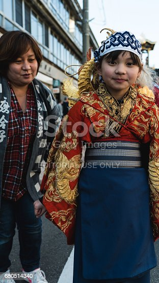 A little girl wears traditional kimono for a festival. Her mother is standing by.