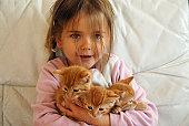little girl holding 3 orange kitten, focus on girl's face