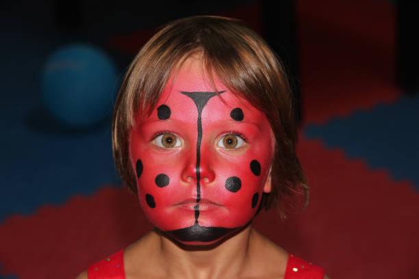 Little girl with ladybug face paint stock photo