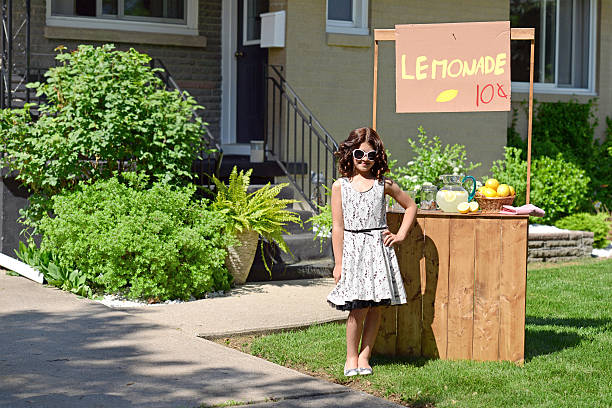 little girl with lemonade stand little girl with lemonade stand in front of house lemonade stand stock pictures, royalty-free photos & images