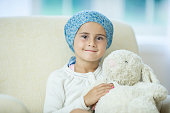 A little girl with cancer is sitting on a chair with her stuffed animal in the hospital. She is wearing a bandana and is smiling while looking at the camera.
