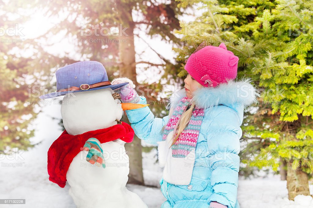 Little girl with make snowball in the winter park stock photo