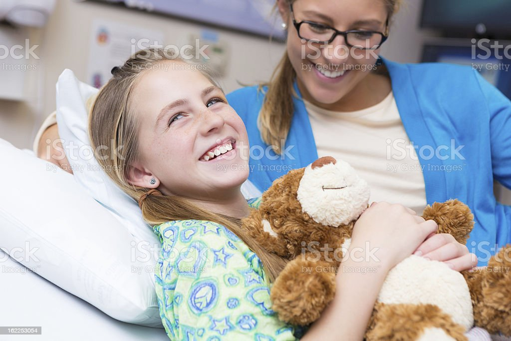 Little girl with mom and teddy bear in children's hospital stock photo