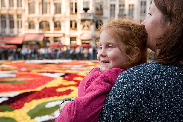 Little girl with mother admiring a flowerbed stock photo