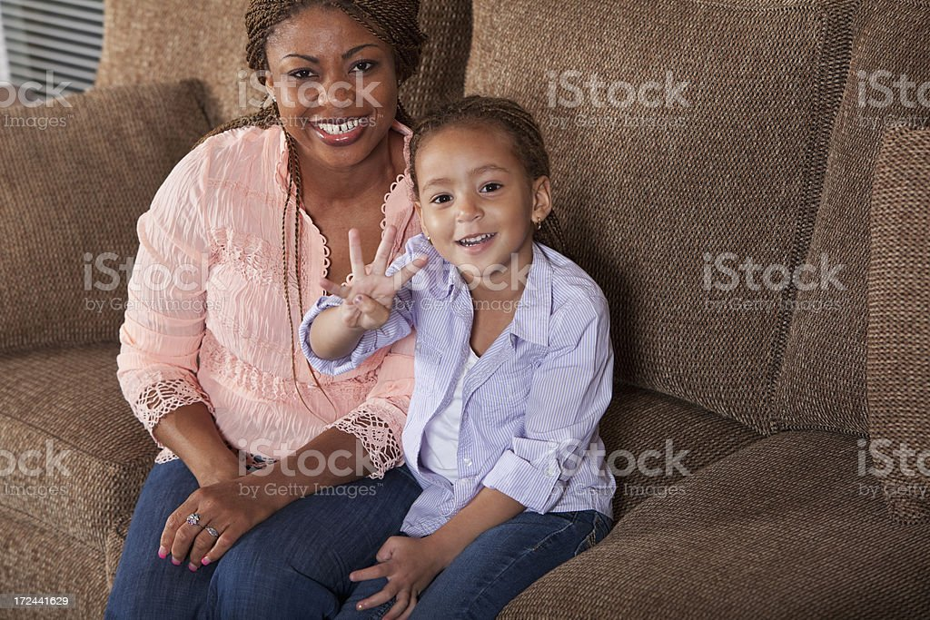 Little girl with mother on sofa royalty-free stock photo