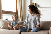 istock Little girl with mother sitting in lotus pose on couch 1257955463