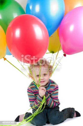 istock Little girl with multicolored air balloons sitting 465680661