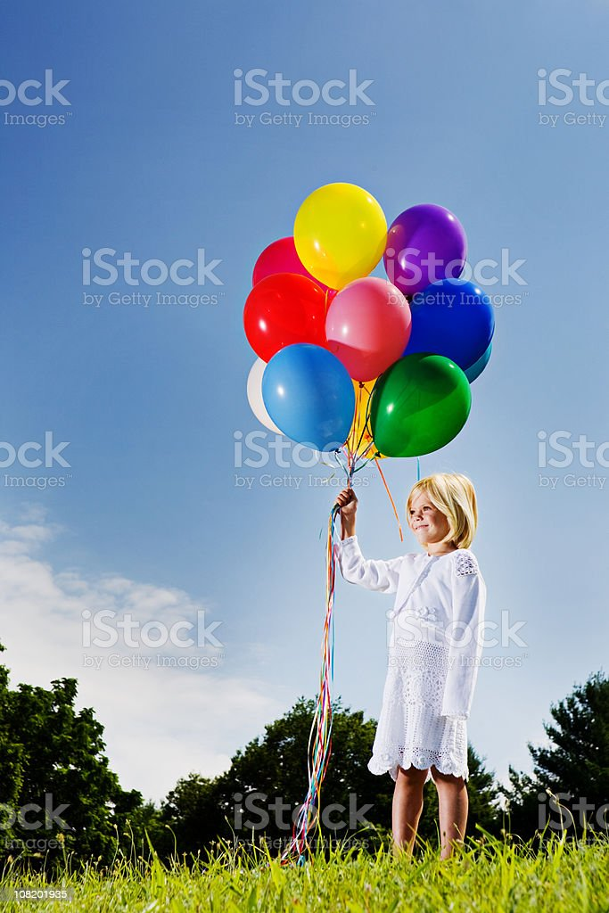 Little girl with multicolored balloons stands smiling royalty-free stock photo