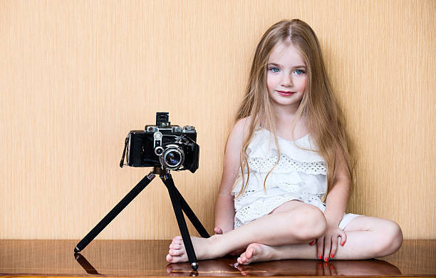Little girl with oldest camera stock photo