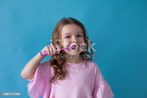 little girl without a tooth with a toothbrush dent