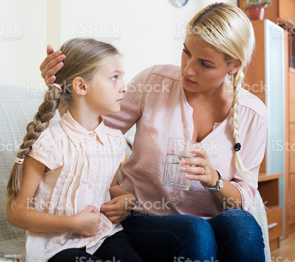 Little girl with pain in belly and worried mother indoors stock photo