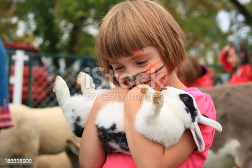 little girl with painted tiger face holds rabbit