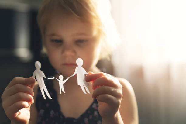 little girl with paper family in hands. concept of divorce, custody and child abuse stock photo
