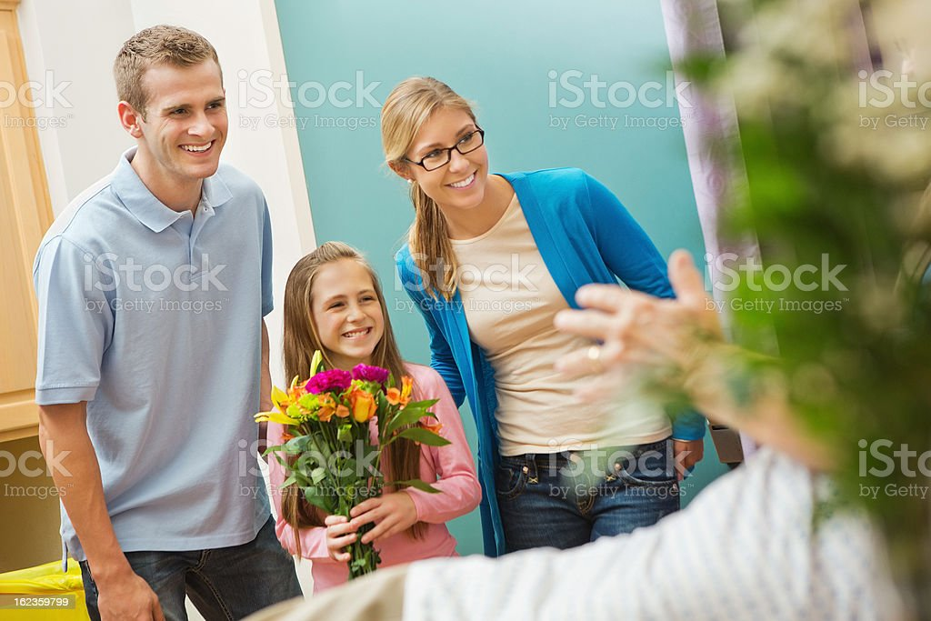 Little girl with parents visiting sick grandfather in hospital stock photo